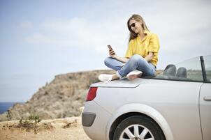 woman-in-yellow-blouse-and-blue-jeans-taking-selfie-while-787472